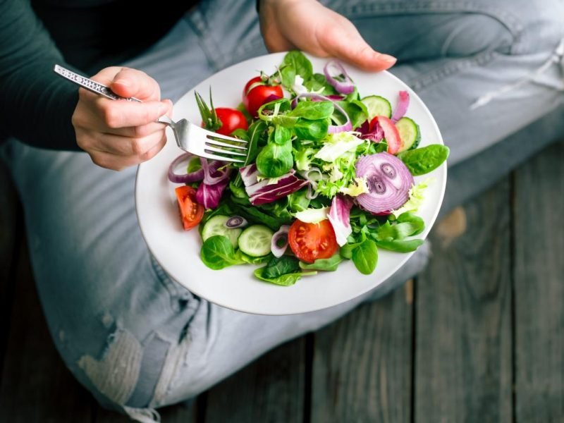 a person sitting on the floor eating a healthy salad 800x600 - What to Avoid to Maintain a Healthy Liver