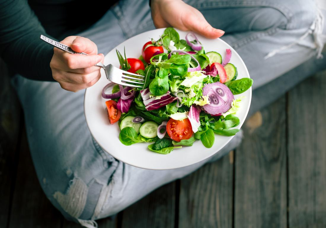 a person sitting on the floor eating a healthy salad - What to Avoid to Maintain a Healthy Liver
